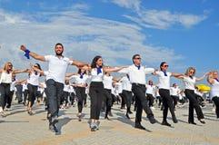 Άνθρωποι στα άσπρα πουκάμισα που προσπαθούν να κερδίσει ένα παγκόσμιο ρεκόρ Guiness για το χορό Hasapiko στοκ εικόνες