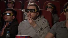 Άνθρωποι στα τρισδιάστατα γυαλιά στον κινηματογράφο Το άτομο στα τρισδιάστατα ποτήρια τρώει το λαϊκό καλαμπόκι απόθεμα βίντεο