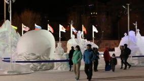 Άνθρωποι στα χιονώδη γλυπτά στην πόλη πάγου τη νύχτα απόθεμα βίντεο