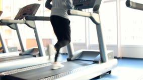 Άνθρωποι στην άσκηση γυμναστικής Τρέξιμο σε μια μηχανή Από την εστίαση φιλμ μικρού μήκους