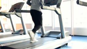 Άνθρωποι στην άσκηση γυμναστικής Τρέξιμο σε μια μηχανή απόθεμα βίντεο