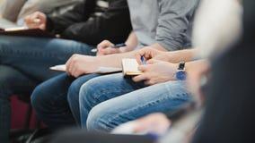 Άνθρωποι στην επιχειρησιακή αίθουσα παρουσίασης ν στη διάλεξη και τη λήψη των σημειώσεων - άνθρωποι που γράφουν στα σημειωματάριά Στοκ Εικόνες
