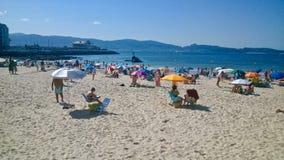 Άνθρωποι στην παραλία Sanxenxo Ισπανία με Madama de Silgar στο υπόβαθρο στοκ εικόνα