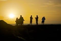 Άνθρωποι στην παραλία κατά τη διάρκεια του ηλιοβασιλέματος στοκ εικόνες