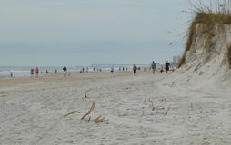 Άνθρωποι στην παραλία κοντά στον αμμόλοφο Στοκ Φωτογραφίες