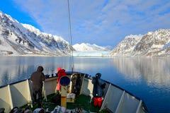 Άνθρωποι στη βάρκα Χειμερινό βουνό με το χιόνι, μπλε πάγος παγετώνων με τη θάλασσα στο πρώτο πλάνο μπλε λευκό ουρανού σύννεφων Χι Στοκ Εικόνα