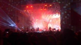Άνθρωποι στη συναυλία με μια μεγάλη σκηνή υπαίθρια απόθεμα βίντεο