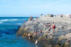 Άνθρωποι στη δύσκολη ακτή ενός ωκεανού Στοκ Εικόνα