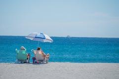 2 άνθρωποι στις καρέκλες παραλιών στην άμμο σε μια παραλία στη Φλώριδα Στοκ Εικόνες