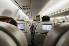 Άνθρωποι στο αεροπλάνο, που κάθεται στα καθίσματά τους που προσέχουν τη TV στοκ εικόνες