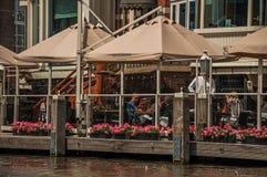 Άνθρωποι στο εστιατόριο δίπλα στο κανάλι σε μια ηλιόλουστη ημέρα στο Άμστερνταμ Στοκ Φωτογραφία