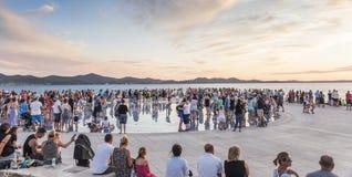 Άνθρωποι στο ηλιοβασίλεμα εκτός από τη θάλασσα στον κυκλικό χαιρετισμό εγκαταστάσεων ηλιακών πλαισίων στον ήλιο από τον αρχιτέκτο Στοκ Εικόνες