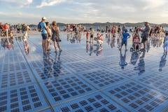 Άνθρωποι στο ηλιοβασίλεμα εκτός από τη θάλασσα στον κυκλικό χαιρετισμό εγκαταστάσεων ηλιακών πλαισίων στον ήλιο από τον αρχιτέκτο Στοκ φωτογραφία με δικαίωμα ελεύθερης χρήσης