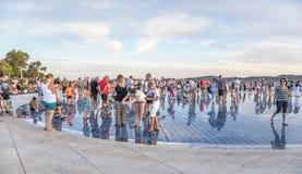 Άνθρωποι στο ηλιοβασίλεμα εκτός από τη θάλασσα στον κυκλικό χαιρετισμό εγκαταστάσεων ηλιακών πλαισίων στον ήλιο από τον αρχιτέκτο Στοκ εικόνες με δικαίωμα ελεύθερης χρήσης