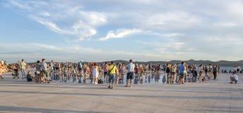 Άνθρωποι στο ηλιοβασίλεμα εκτός από τη θάλασσα στον κυκλικό χαιρετισμό εγκαταστάσεων ηλιακών πλαισίων στον ήλιο από τον αρχιτέκτο Στοκ Εικόνα