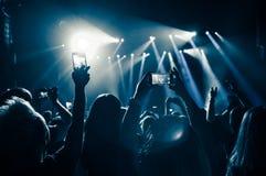 Άνθρωποι στο πλήθος σε μια συναυλία με τα smartphons στα χέρια στοκ φωτογραφία