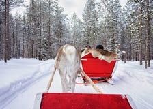 Άνθρωποι στο σαφάρι τροχόσπιτων ταράνδων στο χειμερινό δάσος στο Ροβανιέμι Στοκ Εικόνα