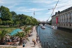 Άνθρωποι στο φραγμό παραλιών δίπλα στο ξεφάντωμα ποταμών με τις βάρκες τουριστών και το τ Στοκ Εικόνες