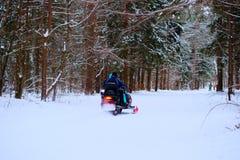 Άνθρωποι στο χειμερινό δάσος, γύρος σε ένα όχημα για το χιόνι και να κάνει σκι Στοκ φωτογραφίες με δικαίωμα ελεύθερης χρήσης