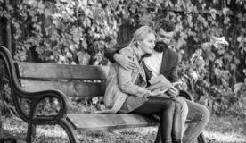 Άνθρωποι συνεδρίασης με τα παρόμοια ενδιαφέροντα Ο άνδρας και η γυναίκα κάθονται το πάρκο πάγκων Διαβάστε το ίδιο βιβλίο από κοιν στοκ φωτογραφίες με δικαίωμα ελεύθερης χρήσης