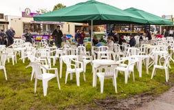Άνθρωποι όλων των ηλικιών που τρώνε και που πίνουν τα ποτά σε έναν λασπώδη τομέα Στοκ Εικόνες