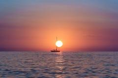 Άνοδος ήλιων στον ωκεανό με μια βάρκα που επιπλέει μπροστά από τον ήλιο Στοκ Φωτογραφίες