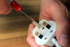 Άνοιγμα ενός βρετανικού 13 amp βουλώματος για να αλλάξει τη θρυαλλίδα στοκ εικόνες