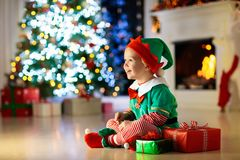 Άνοιγμα παιδιών παρόν στο χριστουγεννιάτικο δέντρο στο σπίτι Παιδί στο κοστούμι νεραιδών με τα δώρα και τα παιχνίδια Χριστουγέννω στοκ φωτογραφίες
