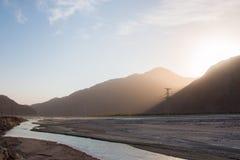Άνοδοι ήλιων πίσω από το βουνό πέρα από μια κοιλάδα ποταμών Στοκ Φωτογραφίες