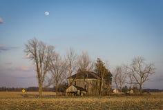 Άνοδοι φεγγαριών πέρα από ένα εγκαταλειμμένο αγροτικό αγροτικό σπίτι Στοκ Εικόνα