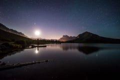 Άνοδοι φεγγαριών πέρα από τη λίμνη στα δύσκολα βουνά Στοκ Φωτογραφία