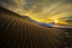 Άνοδος ήλιων στους αμμόλοφους άμμου στα πλαίσια της απόμακρων ζωηρόχρωμων σειράς βουνών και του ουρανού ανατολής, Ladakh, το Ιμαλ Στοκ Εικόνα