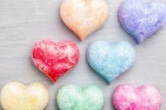 άνδρας αγάπης φιλιών έννοιας στη γυναίκα Ζωηρόχρωμες καρδιές στο γκρίζο υπόβαθρο Στοκ Φωτογραφίες