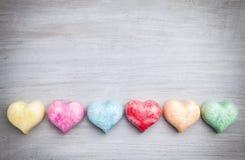 άνδρας αγάπης φιλιών έννοιας στη γυναίκα Ζωηρόχρωμες καρδιές στο γκρίζο υπόβαθρο Στοκ Φωτογραφία