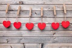 άνδρας αγάπης φιλιών έννοιας στη γυναίκα Καρδιές που κρεμούν σε μια σειρά Στοκ εικόνα με δικαίωμα ελεύθερης χρήσης