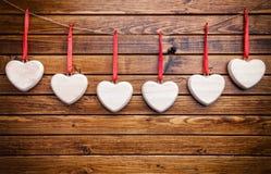 άνδρας αγάπης φιλιών έννοιας στη γυναίκα Καρδιές που κρεμούν σε μια σειρά Στοκ εικόνες με δικαίωμα ελεύθερης χρήσης