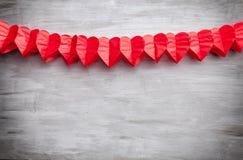 άνδρας αγάπης φιλιών έννοιας στη γυναίκα Καρδιές που κρεμούν στο γκρίζο υπόβαθρο Στοκ εικόνες με δικαίωμα ελεύθερης χρήσης