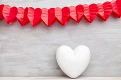 άνδρας αγάπης φιλιών έννοιας στη γυναίκα Καρδιές που κρεμούν στο γκρίζο υπόβαθρο Στοκ εικόνα με δικαίωμα ελεύθερης χρήσης