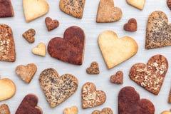 άνδρας αγάπης φιλιών έννοιας στη γυναίκα Ποικιλία των μπισκότων καρδιών στο γκρίζο υπόβαθρο Στοκ Εικόνες