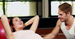 Άνδρας εκπαιδευτών που βοηθά τη γυναίκα που κάνει τις κρίσιμες στιγμές της απόθεμα βίντεο
