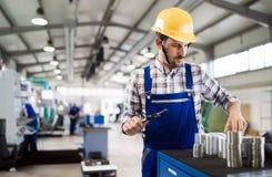Άνδρας εργαζόμενος και επιθεώρηση ποιοτικού ελέγχου στο εργοστάσιο Στοκ Εικόνα