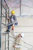 Άνδρας εργαζόμενος που δίνει το τρυπάνι στη γυναίκα στο ικρίωμα στο εργοτάξιο οικοδομής Στοκ φωτογραφία με δικαίωμα ελεύθερης χρήσης