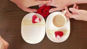 Άνδρας και γυναίκα κατά μια ημερομηνία σε έναν καφέ πιείτε τον καφέ και το κέικ Δίνει τα λουλούδια απόθεμα βίντεο