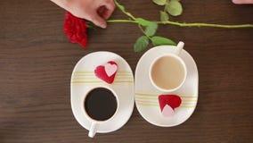 Άνδρας και γυναίκα κατά μια ημερομηνία σε έναν καφέ πιείτε τον καφέ και το κέικ Δίνει τα λουλούδια φιλμ μικρού μήκους