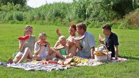 άνδρας και γυναίκα με τέσσερα παιδιά στο πικ-νίκ από κοινού απόθεμα βίντεο