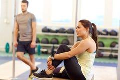 Άνδρας και γυναίκα με τον ιχνηλάτη ποσοστού καρδιών στη γυμναστική Στοκ φωτογραφία με δικαίωμα ελεύθερης χρήσης