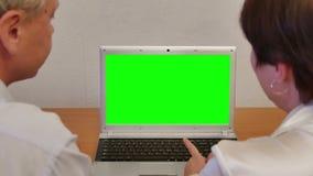 Άνδρας και γυναίκα με το πράσινο lap-top οθόνης φιλμ μικρού μήκους