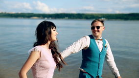 Άνδρας και γυναίκα, νέοι, ευτυχές παντρεμένο ενήλικο ζευγάρι που έχουν τη διασκέδαση και που παίζουν στην ακτή, παραλία απόθεμα βίντεο