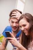 Άνδρας και γυναίκα που έχουν τη διασκέδαση με τα κινητά τηλέφωνά τους Στοκ Εικόνες