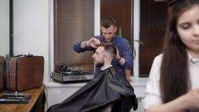 Άνδρας και γυναίκα που εργάζονται στο barbershop που κάνει τη μοντέρνη τρίχα στους πελάτες που κάθονται στην καρέκλα απόθεμα βίντεο